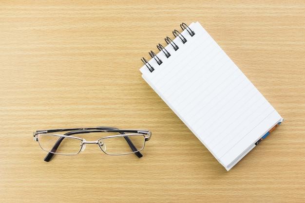 Brillen und notizblock mit leerer seite