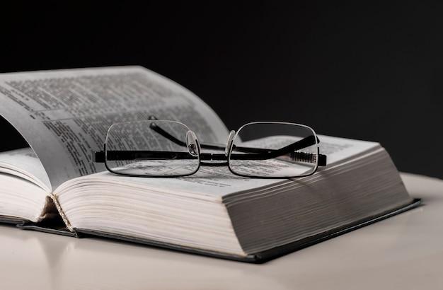 Brillen und offenes buch auf schwarzem hintergrund