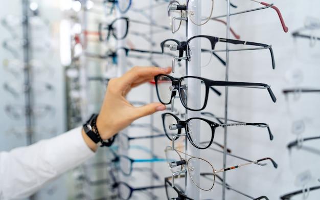 Brillenreihe bei einem optiker. brillengeschäft. stellen sie sich mit brille in den laden der optik. frauenhand wählt brillen. sehkraftkorrektur.