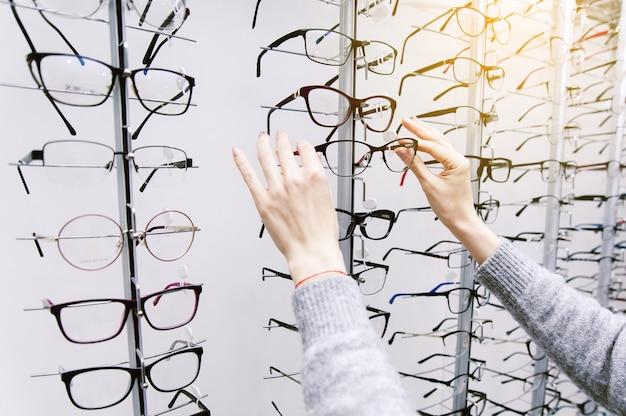Brillenreihe bei einem optiker. brillengeschäft. stellen sie sich mit brille in den laden der optik.