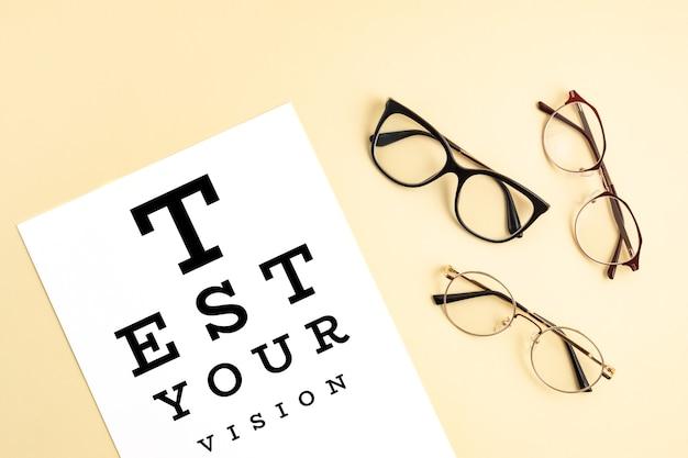 Brillensammlung mit sehtesttisch. optischer laden, brillenauswahl, sehtest, sichtprüfung beim optiker, modeaccessoire-konzept. draufsicht, flach liegen