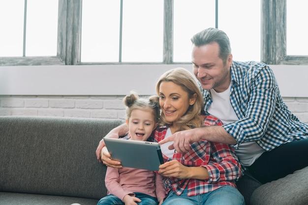 Bringen sie auf digitale tablette mit ihrer lächelnden frau und tochter zu hause zeigen hervor