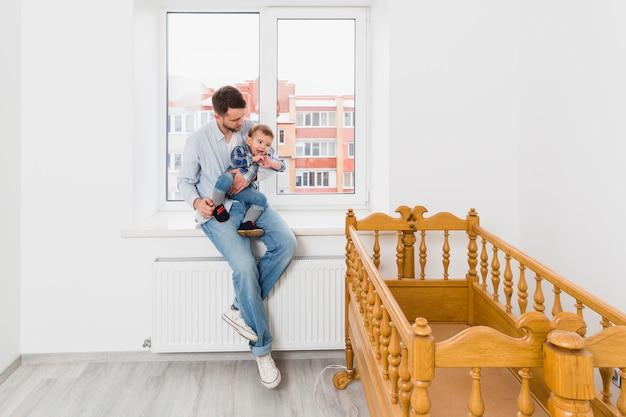 Bringen sie das tragen seines babysohns hervor, der auf dem fensterbrett sitzt, das hölzerne leere krippe betrachtet