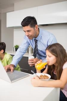 Bringen sie die verwendung des laptops und der kinder hervor, die in der küche frühstücken