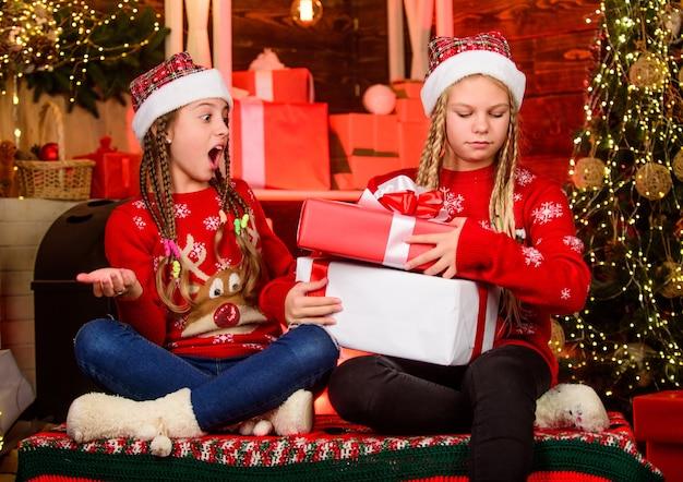 Bringen sie großzügigkeit hervor. weihnachtsgeschenke konzept. schwesternschaft. mädchenfreunde feiern weihnachten. boxtag. schöne ferien. spaß und freude. kinder fröhlicher heiligabend. geschenke teilen. fähigkeit zum teilen.