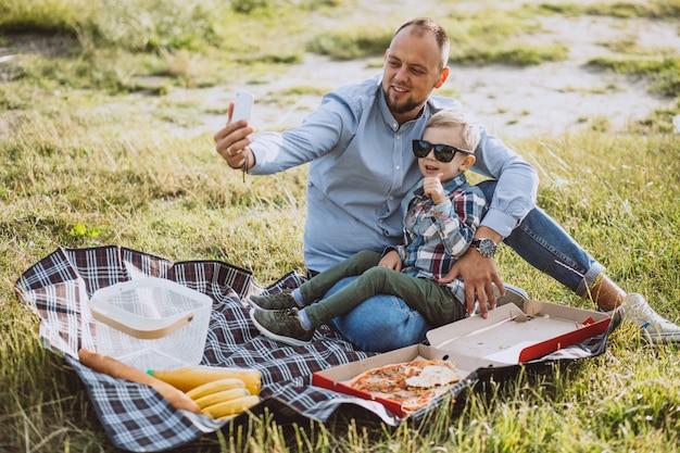 Bringen sie mit seinem sohn hervor, der picknick im park hat