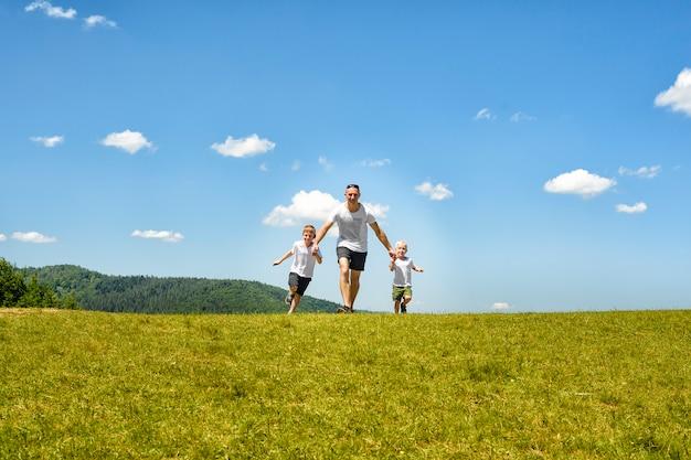 Bringen sie mit zwei kleinkindern hervor, die hand in hand auf dem grünen feld laufen