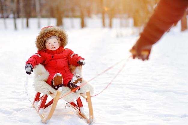 Bringen sie und sein kleinkindsohn hervor, der spaß im winterpark hat. spiele mit frischem schnee