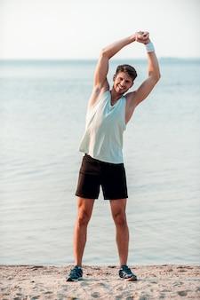 Bringt seine fitness in schwung. lächelnder junger muskulöser mann, der beim stehen am flussufer trainiert