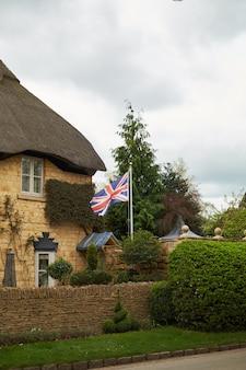 Britische flagge des alten englischen hauses cotswold stone cottage