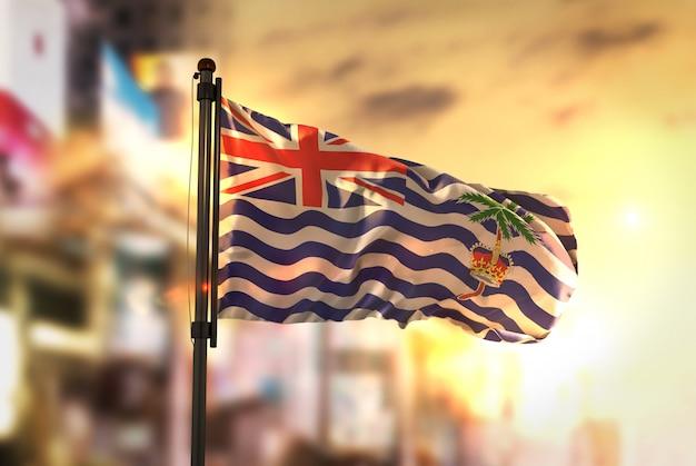Britische indische ozean territorium flagge gegen stadt unscharfen hintergrund bei sonnenaufgang hintergrundbeleuchtung
