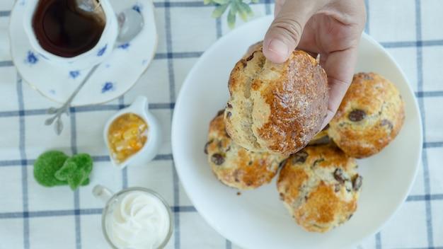 Britische scones mit frischkäse, orangenmarmelade und einer tasse kaffee auf blauer robben-tischdecke. zoom-makro.