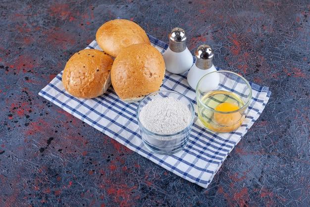 Brötchen, eine schüssel mehl und eine schüssel ei auf geschirrtuch auf blau.