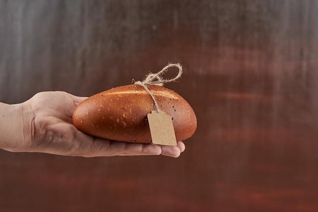 Brötchen in der hand des bäckers mit etikett.