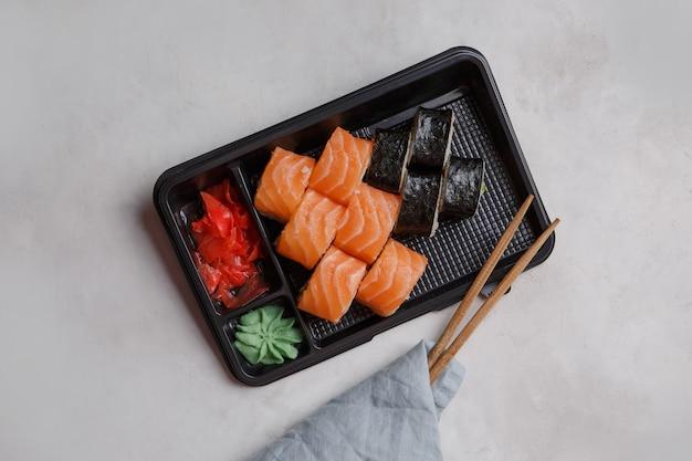 Brötchen in einem plastikbehälter, rosa ingwer, wasabi, sushi-lieferkonzept. japanisches essen bestellen