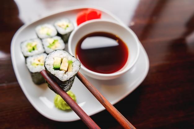 Brötchen in nori-algen mit avocado, eingelegtem ingwer und sojasauce. asiatische küche, traditionelles gericht - sushi.