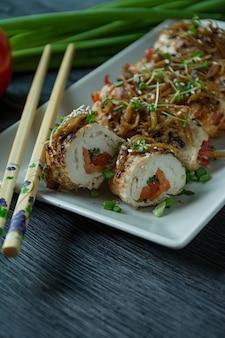 Brötchen mit frischer hähnchenbrust mit gemüse, karottenscheiben, paprika auf einem dunklen schneidebrett.