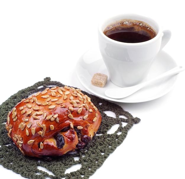 Brötchen mit rosinen und sonnenblumenkernen mit kaffeetasse auf weißem hintergrund