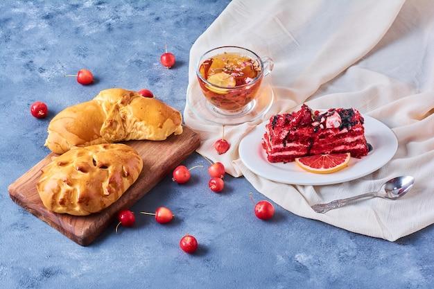 Brötchen mit rotem samtkuchen und tee auf einem holzbrett auf blau