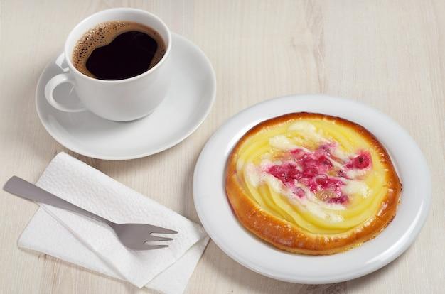 Brötchen mit vanillepudding und beeren in teller und tasse kaffee auf hellem holztisch
