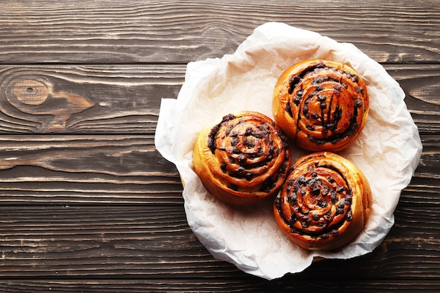 Brötchen mit zimt und schokolade auf braunem holzhintergrund. zimtstange und schwarzer espressokaffee. platz für text. ansicht von oben.