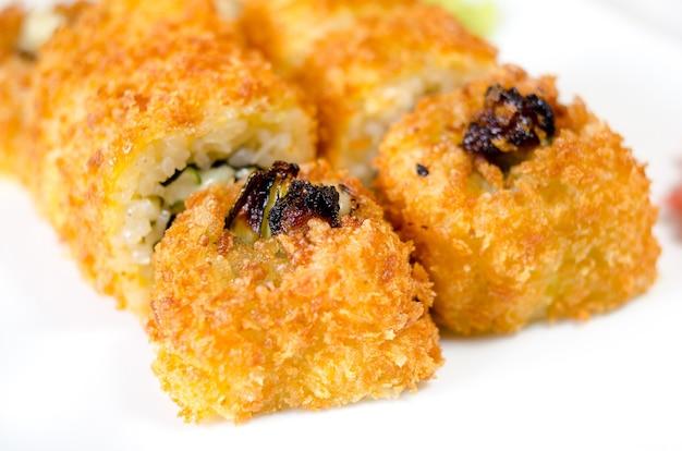 Brötchen, sushi und ingwer auf einem weißen teller und einer hellen oberfläche.