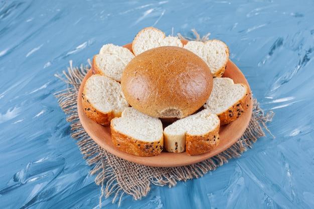 Brötchen und geschnittenes brot auf teller auf leinenserviette auf blau.
