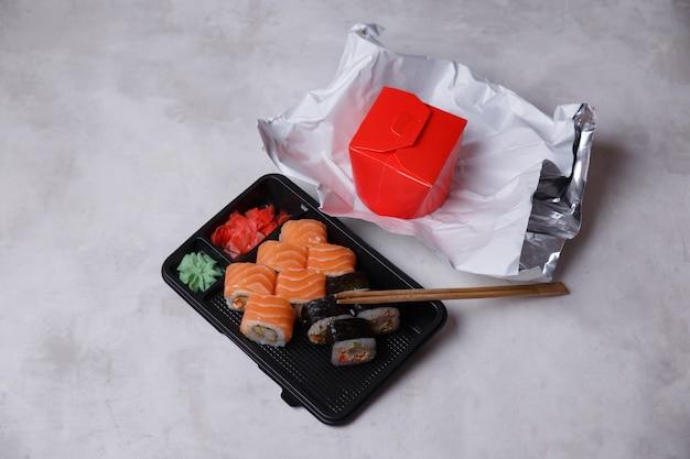 Brötchen zum mitnehmen in plastikbehältern, verschiedene brötchen, nudeln in einer schachtel, sojasauce, rosa ingwer, wasabi, sushi-lieferkonzept. bestellung von lebensmitteln