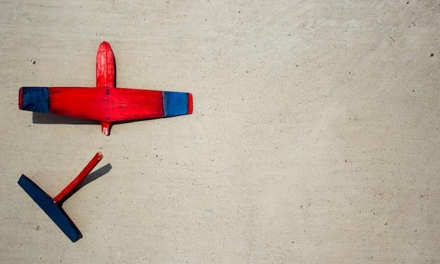 Broken wodden segelflugzeug auf zement liegen