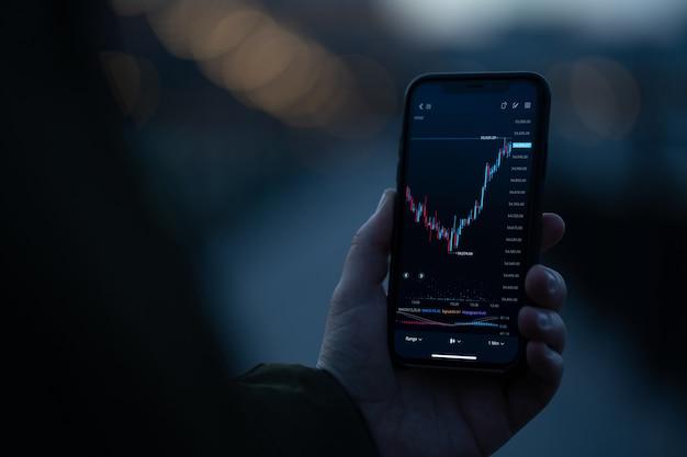 Broker oder investor, der die aktienhandels-app auf dem smartphone verwendet, um den kursfluss an der börse zu analysieren, während er im freien steht. selektiver fokus auf der hand, die handy mit forex-diagramm auf dem bildschirm hält