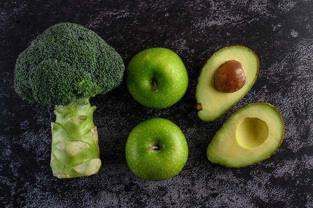 Brokkoli, apfel und avocado auf einem schwarzen zementboden.