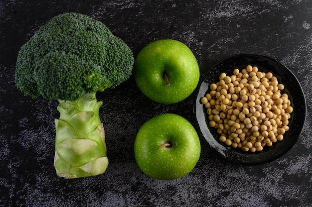 Brokkoli, apfel und sojabohnen auf einem schwarzen zementboden.