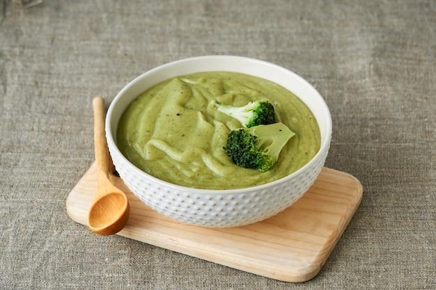 Brokkoli-cremesuppe in einer weißen schüssel auf einem textilhintergrund