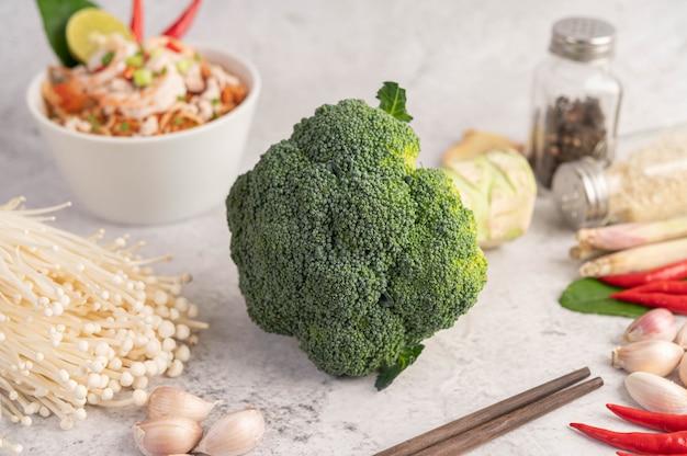 Brokkoli, goldener nadelpilz, essstäbchen, knoblauch und chilischoten auf weißem zementboden