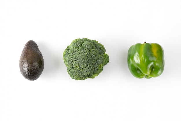 Brokkoli, grüner paprika, avocado. kreatives gemüse-layout auf grünem hintergrund