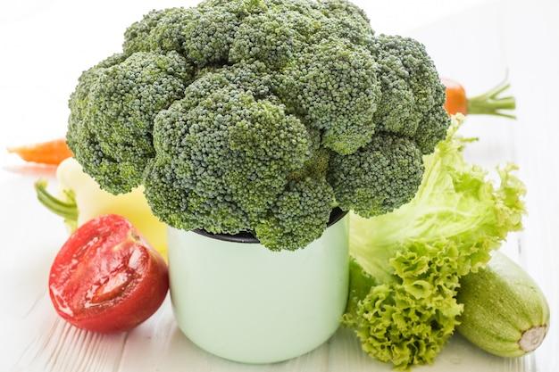 Brokkoli in den teeschalen mit tomate, salat, pfeffer, karotte und zucchini auf einem weißen holztisch