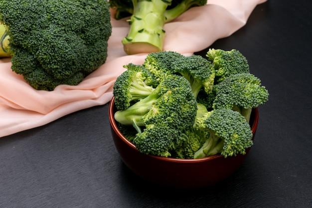 Brokkoli in keramikschale und auf rosa tuch