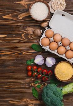 Brokkoli; kirschtomaten; halbierte zwiebel; pilz; knuspriger puffreiskuchen und polentaschüssel auf hölzernem schreibtisch