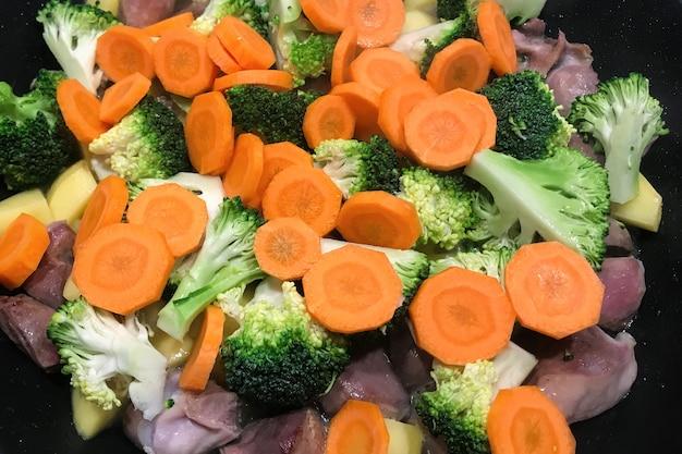 Brokkoli mit karotten und fleisch wird in einer pfanne gekocht