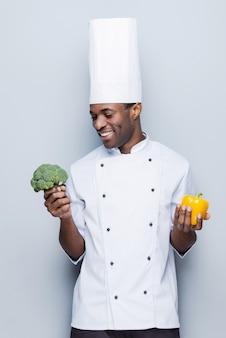 Brokkoli oder paprika? fröhlicher junger afrikanischer koch in weißer uniform