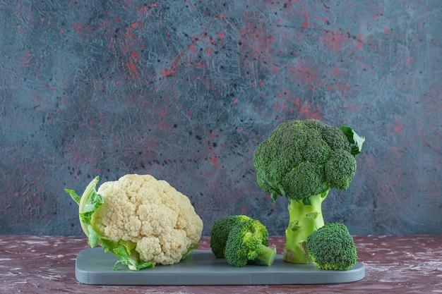 Brokkoli und blumenkohl auf einem brett auf der marmoroberfläche
