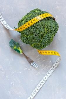 Brokkoli und zentimeter. frisches gemüse, konzept zur gewichtsreduktion, diät, ketogene diät, intermittierendes fasten
