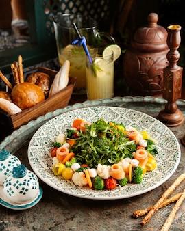 Brokkolisalat mit lachs karotten blumenkohl mozzarellcherry tomaten rucola hausgemachte limonade und brot auf dem tisch
