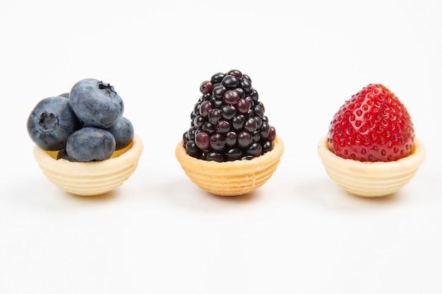Brombeere, blaubeere und erdbeere in einem waffelkorb auf einem weiß.