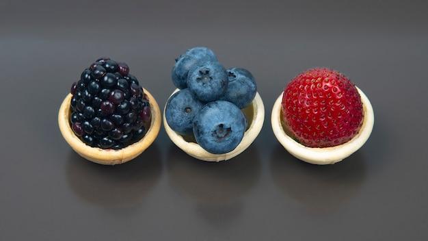 Brombeere, blaubeere und erdbeere in einem waffelkorb auf grauer draufsicht