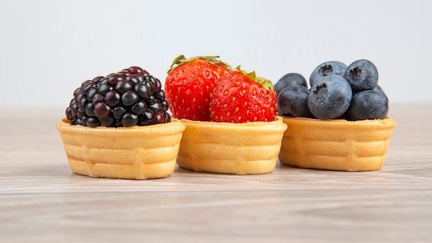 Brombeere, erdbeer-blaubeere in einem waffelkorb. vitamine und gesunde lebensmittel