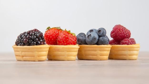 Brombeeren, himbeeren, erdbeeren, blaubeeren in einem waffelkorb. vitamine und gesunde lebensmittel