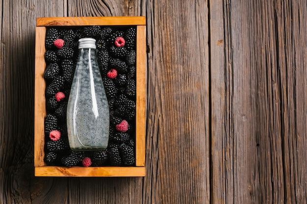 Brombeersaftflasche auf hölzernem hintergrund