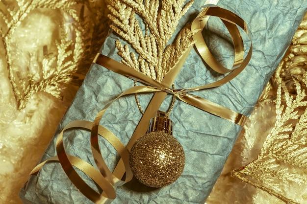 Bronzene neujahrsdekorationen und blaue geschenkbox. ansicht von oben. weihnachtsgrußkarte, natürliche farben.