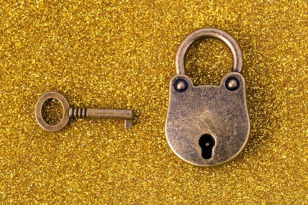 Bronzeschloss und schlüssel über goldenem glitzerhintergrund